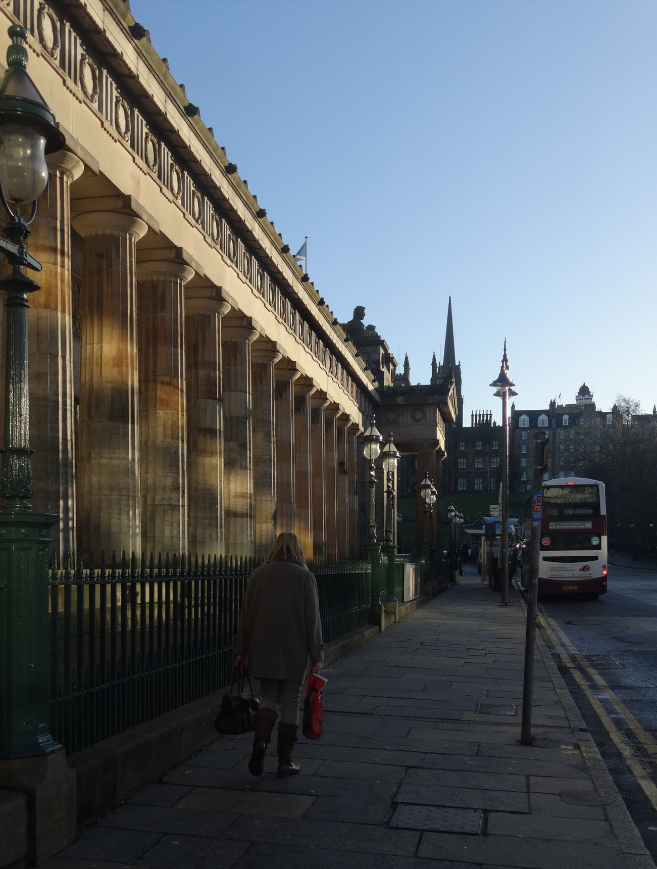 A lady walks up the Mound, winter sun rays playing on the columns of the RSA