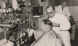 Photographed on the far side is our father shaving a customer.