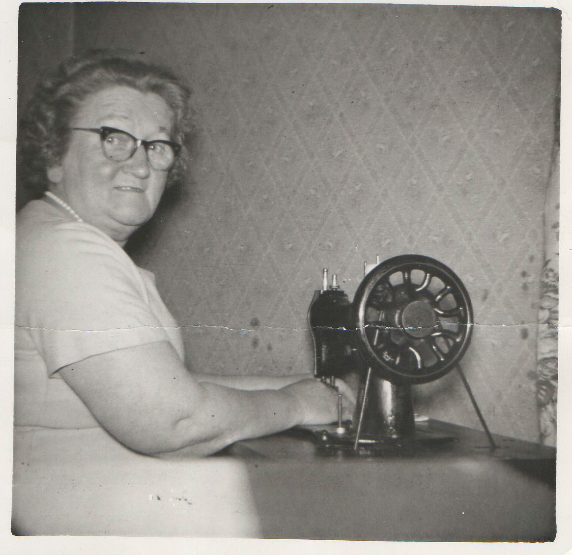 Mother sitting at home in the Well Court working away on her Sewing Machine.