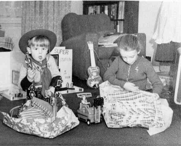 Brother And Sister Unwrapping Presents On Christmas Day c.1955