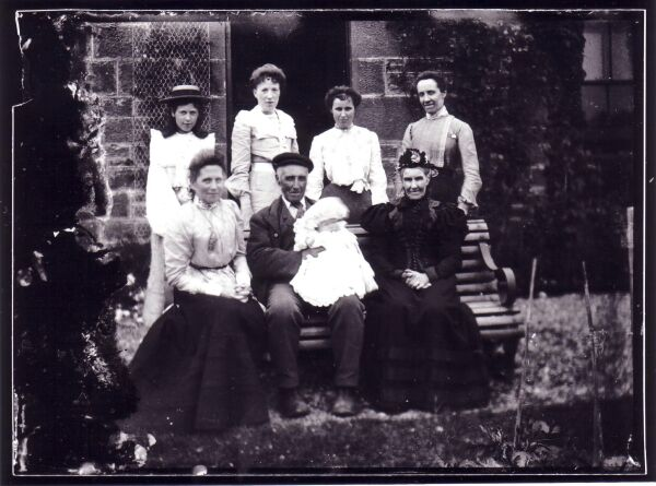 Family Group Portrait Sitting On Bench Outside House c.1900