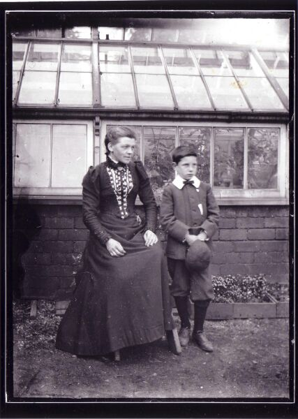 Woman And Boy In Front Of Glasshouse c.1900