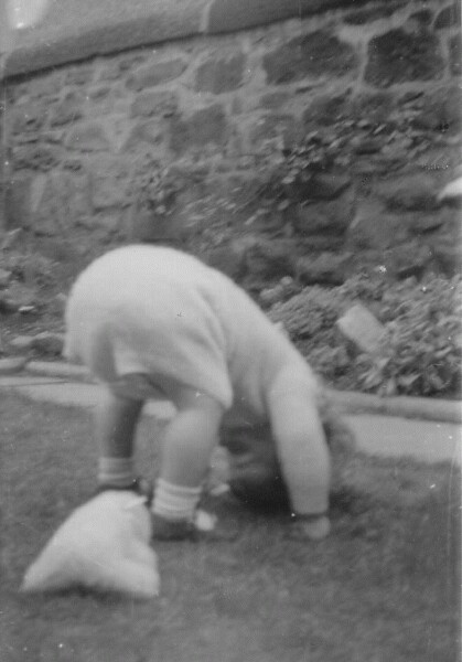 Young Child At Play Looking Through Legs In Garden Of Home At 28 Upper Gilmore Place, July 1963