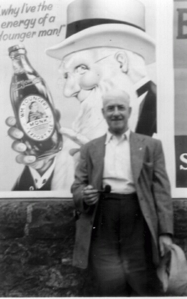 Man With Pipe Standing In Front Of Billboard 1958