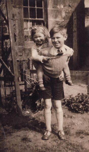 Brother Giving His Little Sister A Cuddyback, April 1946