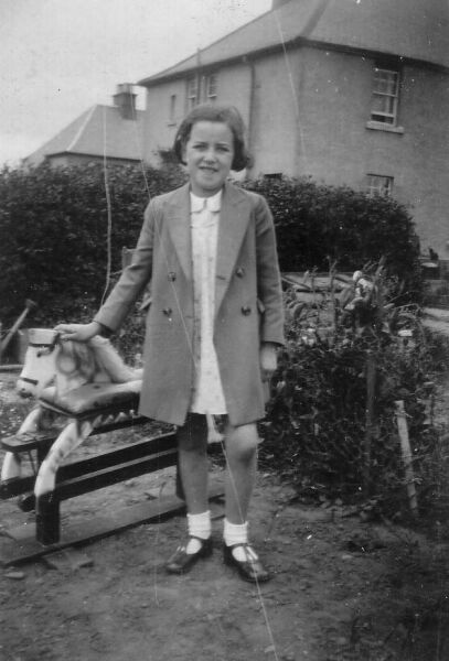 Girl Standing By Rocking Horse In Back Green 1940