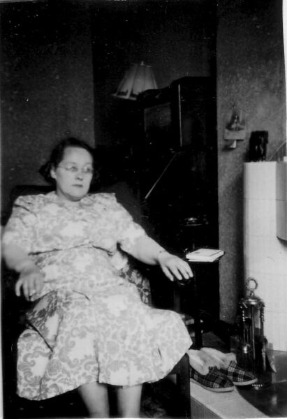 Woman Sitting By Fire With Slippers Warming On Hearth At Home In Piershill Place, early 1960s