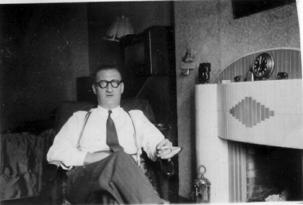 Man Sitting By Fireplace Smoking Cigarette, early 1960s