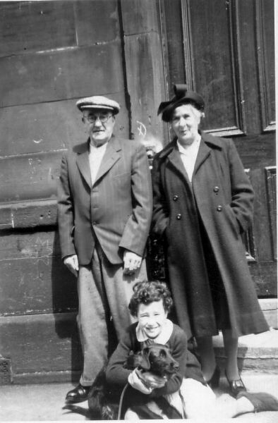 Grandparents With Their Granddaughter And Pet Dog Outside Doorway On Rossie Place 1953