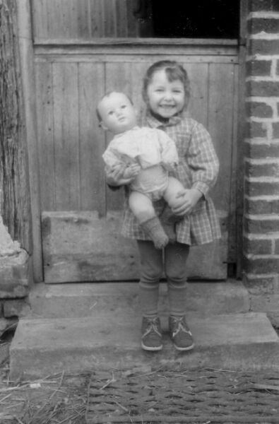 Young French Girl With Doll Standing In Front Of Door To House, Easter 1963