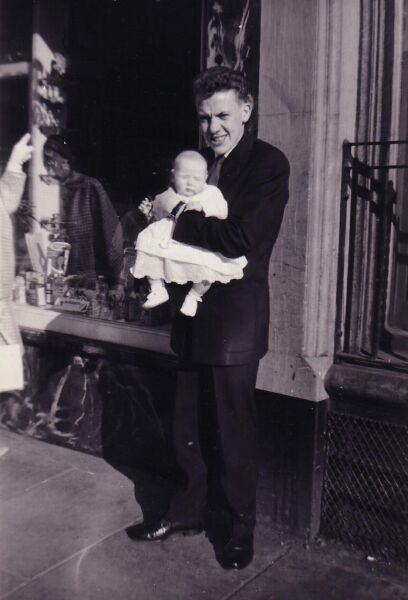 Man Standing Holding Baby Outside Shop Window 1960