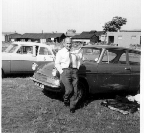 Man Leaning On HIs Ford Anglia On Day Trip To Belhaven 1964