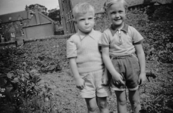 Young Boy And Girl Standing In The Garden 1958
