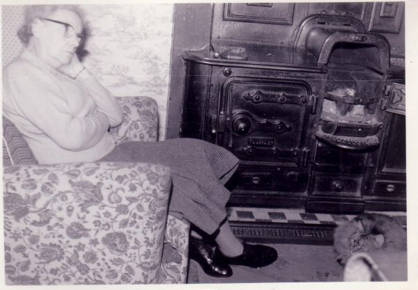 Woman In Sitting Room Armchair By Range Fire 1950s