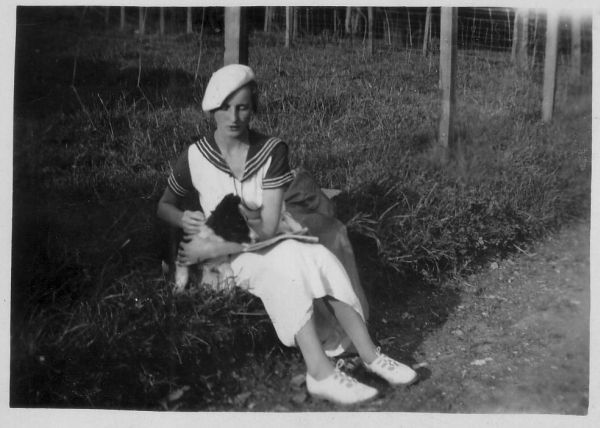 Fashionable Young Woman With Dog Sitting On Grass Verge c.1920
