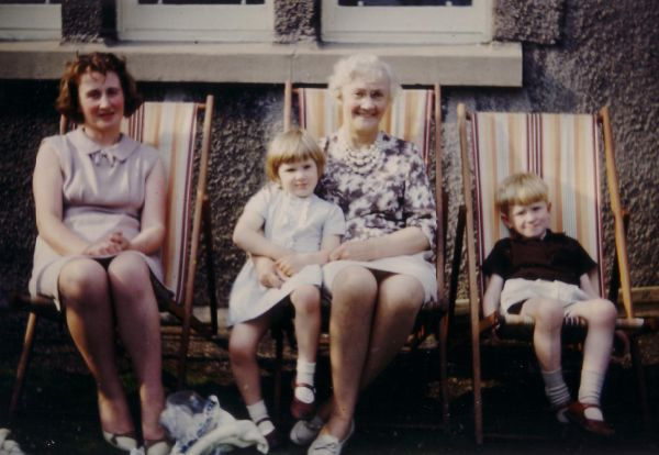 Women And Children Sitting Outside House In Deckchairs 1965