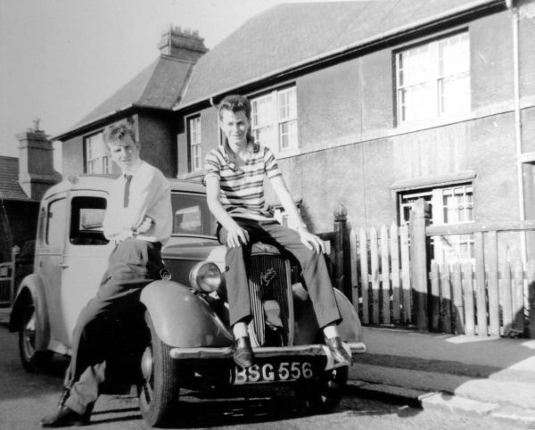 Two Teenagers Sitting On Vintage Car 1960