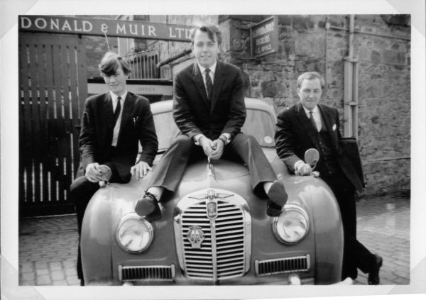 Three Young Men Sitting On Car Outside Distillery c.1965