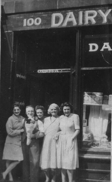 Shop worker with flowers and ladies outside dairy shop 1945