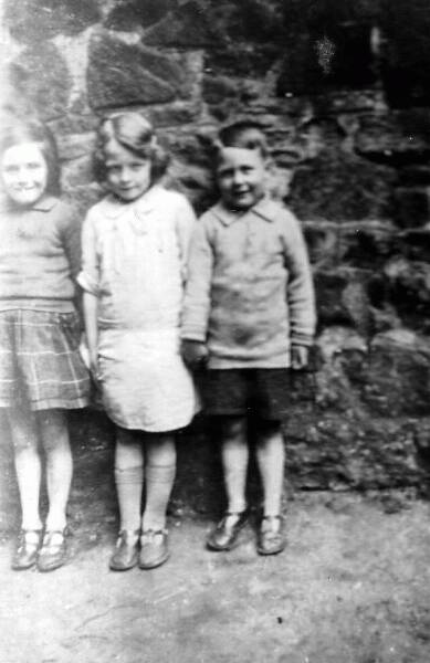 Children standing against wall in back green 1931