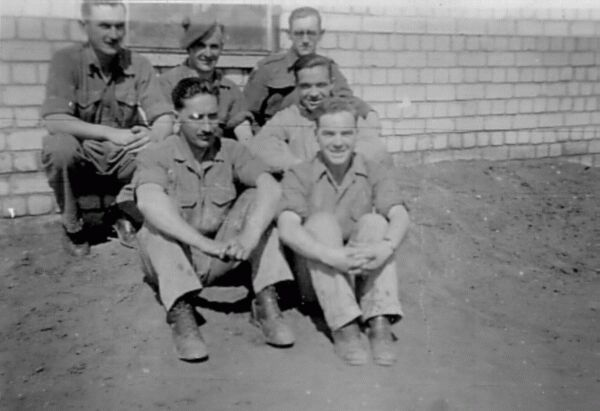 Soldiers Squatting By A Wall 1945