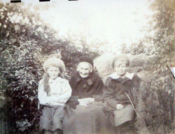 Elderly Woman Sitting In Garden With Her Grand Nieces c.1880