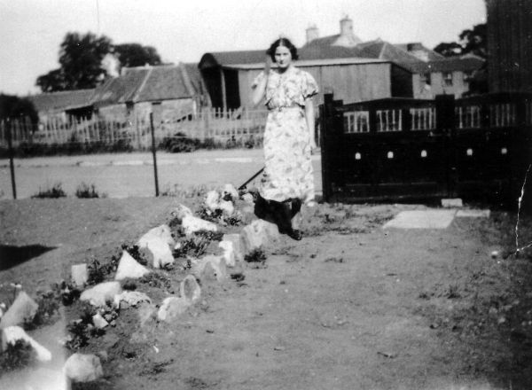 Woman Standing By Rockery In Driveway, late 1930s