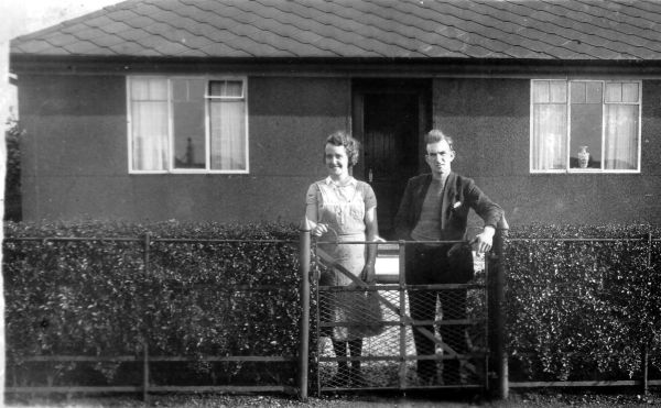 Man And Woman Standing By Front Gate Of House, late 1930s