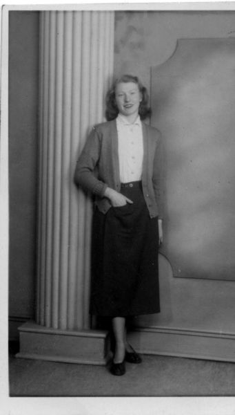 Studio Portrait Young Woman Hand In Pocket Standing By Pillar, August 1953