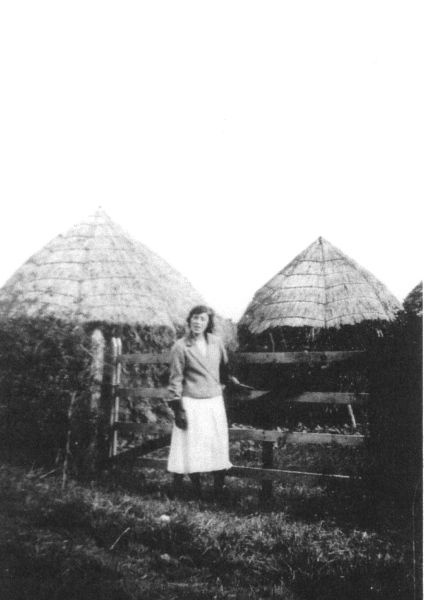 Woman Standing By Gate And Hay Ricks 1930s