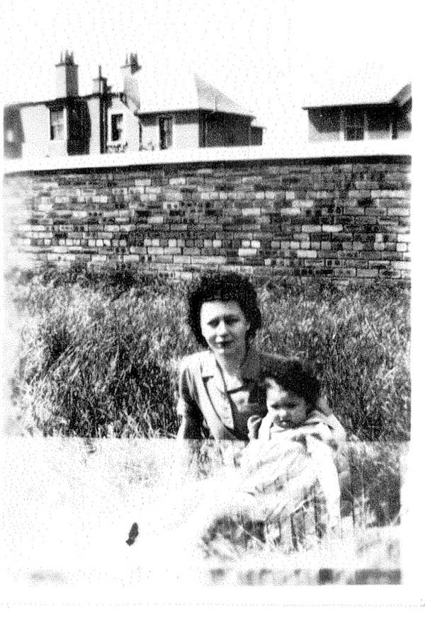 Woman And Child Sitting In Grass By Wall 1941