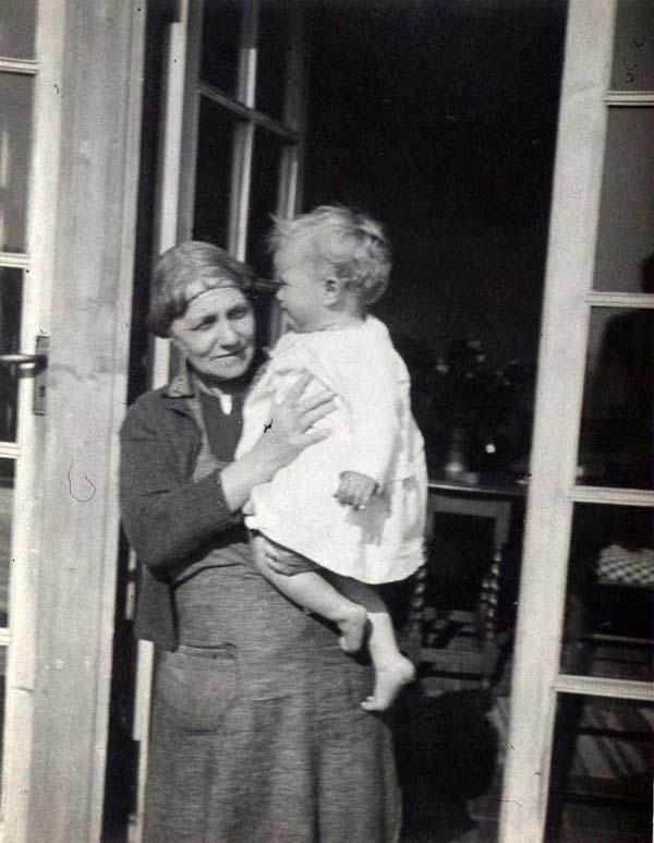 Woman Standing In Doorway Holding Baby 1950s