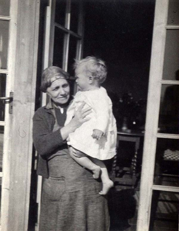 Woman Standing In Doorway Holding Baby 1950s