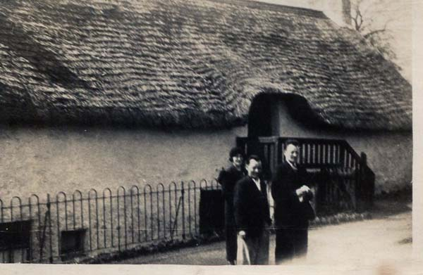 Three People Standing By Thatched Cottage 1930s