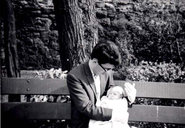 Young Father Sitting Outdoor On Bench Holding Baby Daughter c.1966