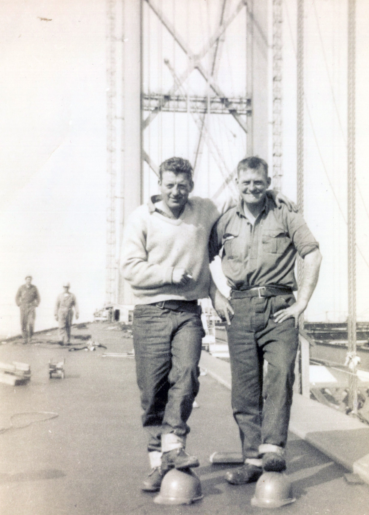 Two Construction Workers Of The Forth Road Bridge With A Foot Each On Their Hard Hats c.1964