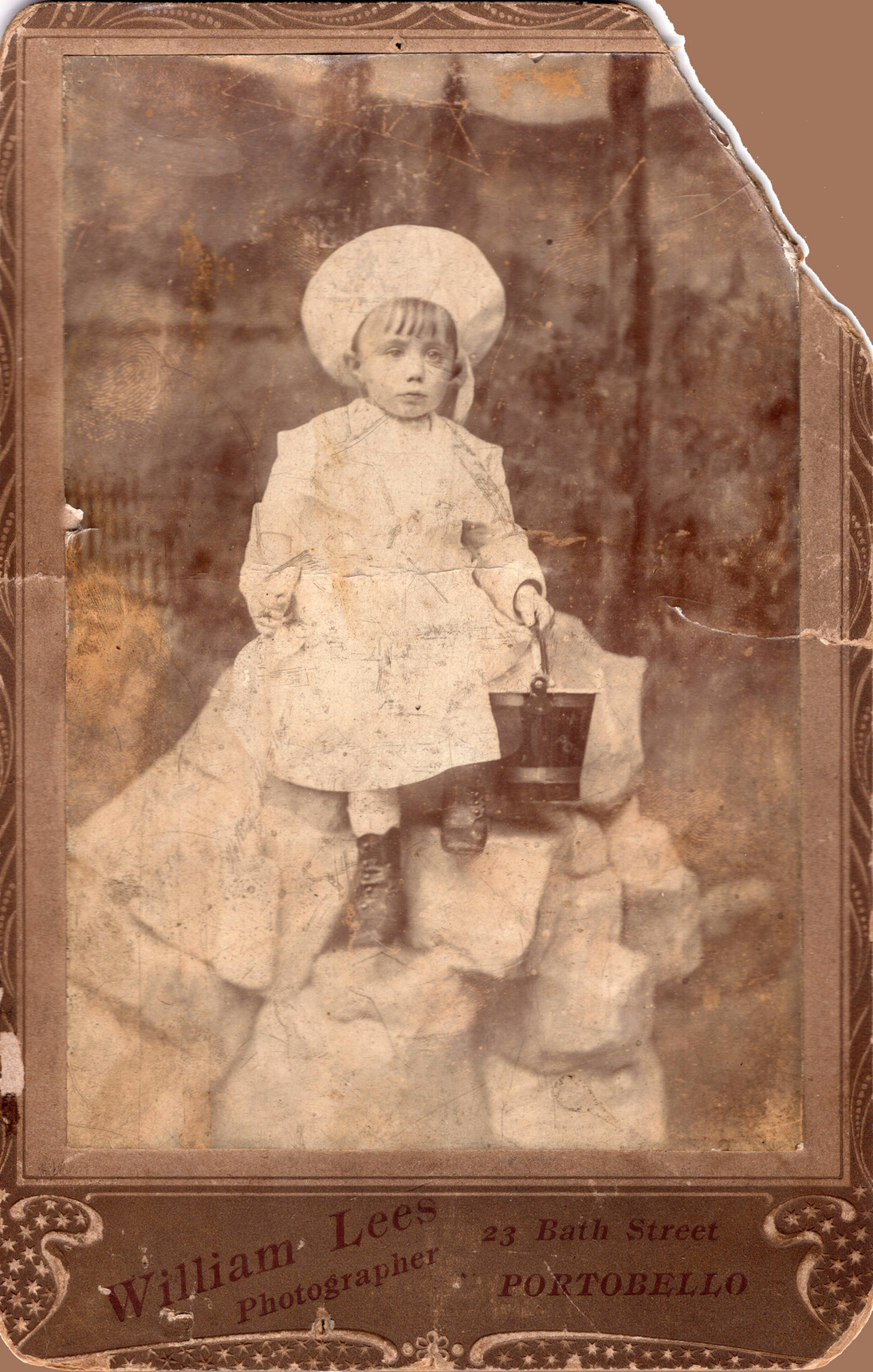 Studio Portrait Child Sitting On Rocks With Bucket And Spade c.1910
