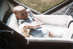 Infant Sitting In Sunlight In Pram With Doll 1960s