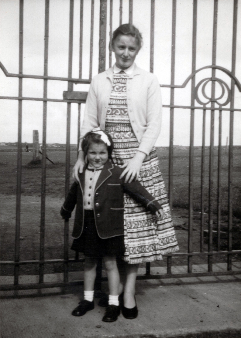 Young Woman With Her Younger Cousin Standing Outside Bignold Park Gate In Orkney c.1956