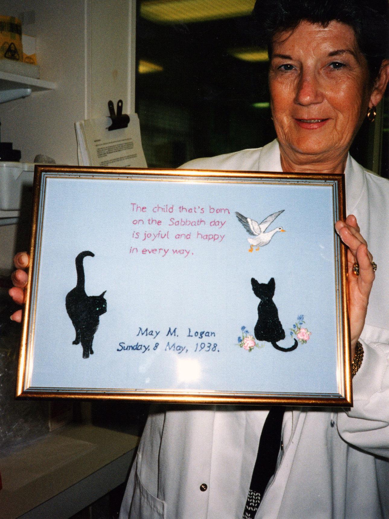 Woman Holding Framed Embroidered Sampler c.1990