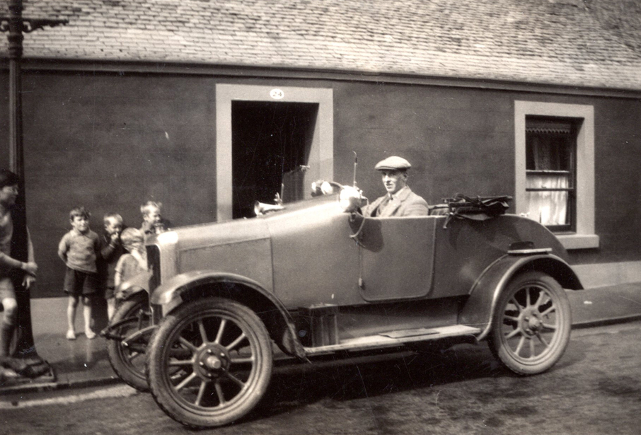 Man Behind Wheel Of Car Children Looking On 1920s