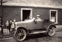 Man Stting Behind Wheel Of Car Children Looking On 1920s
