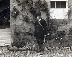 Man Standing In Front Of House With Hammer 1920s