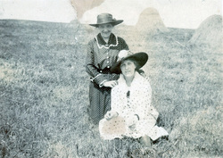 Two Sisters Sitting In A Field With Hayricks c.1920