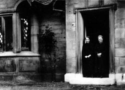 Two Women Standing In Doorway Of House 1940s