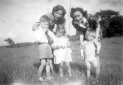 Two Women With Young Children Playing In Field 1950s