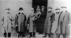 Group Of Men Standing Round Doorway 1930s
