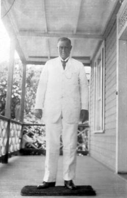 Gentleman In White Suit Standing On Verandah 1920s