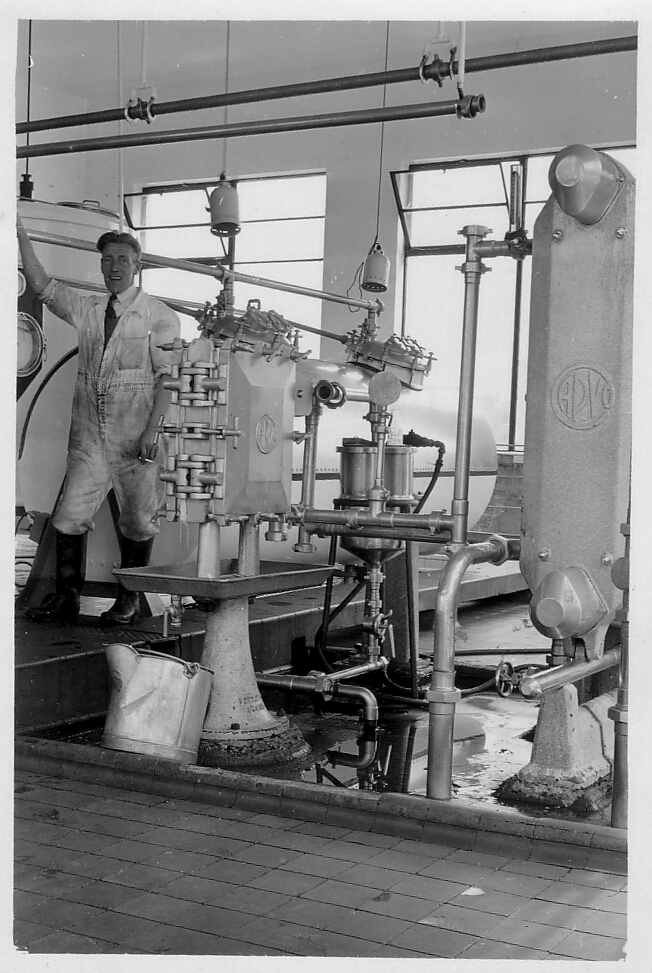 Man Standing Smoking By Dairy Machinery, late 1940s