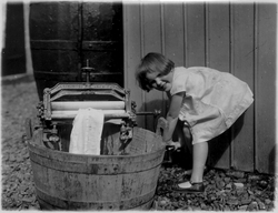 Young Girl On Farm Wringing Cloth Through Mangle, late 1940s